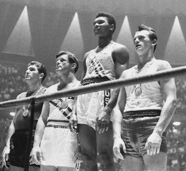 18-year-old Cassius Clay brings home the Gold Medal for the US (Photo Credit: Polish Press Agency (PAP) ([1], #5/28) [Public domain], via Wikimedia Commons