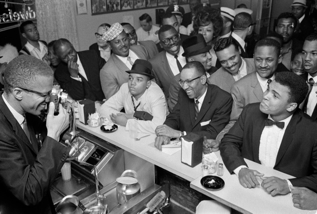 Malcolm X photographs Ali following his victory over Sonny Liston (Photo Credit: E P Houston (Own work) CC BY-SA-4.0, via Wikimedia Commons)